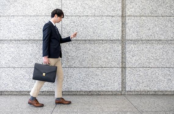 スマートフォンを見ながら歩く男性