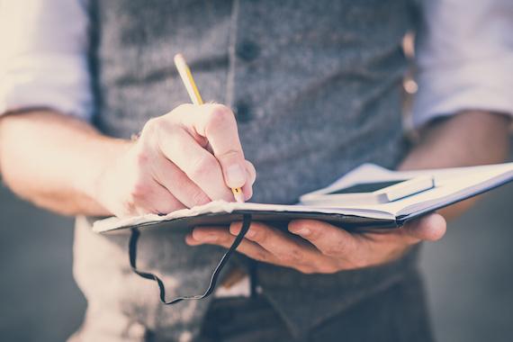 ノートに字を書く男性
