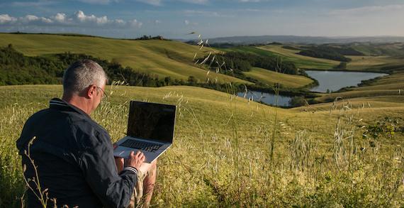 野原でパソコンを使う男性