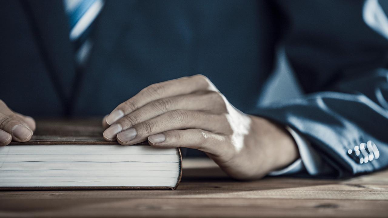 本に手を添える男性