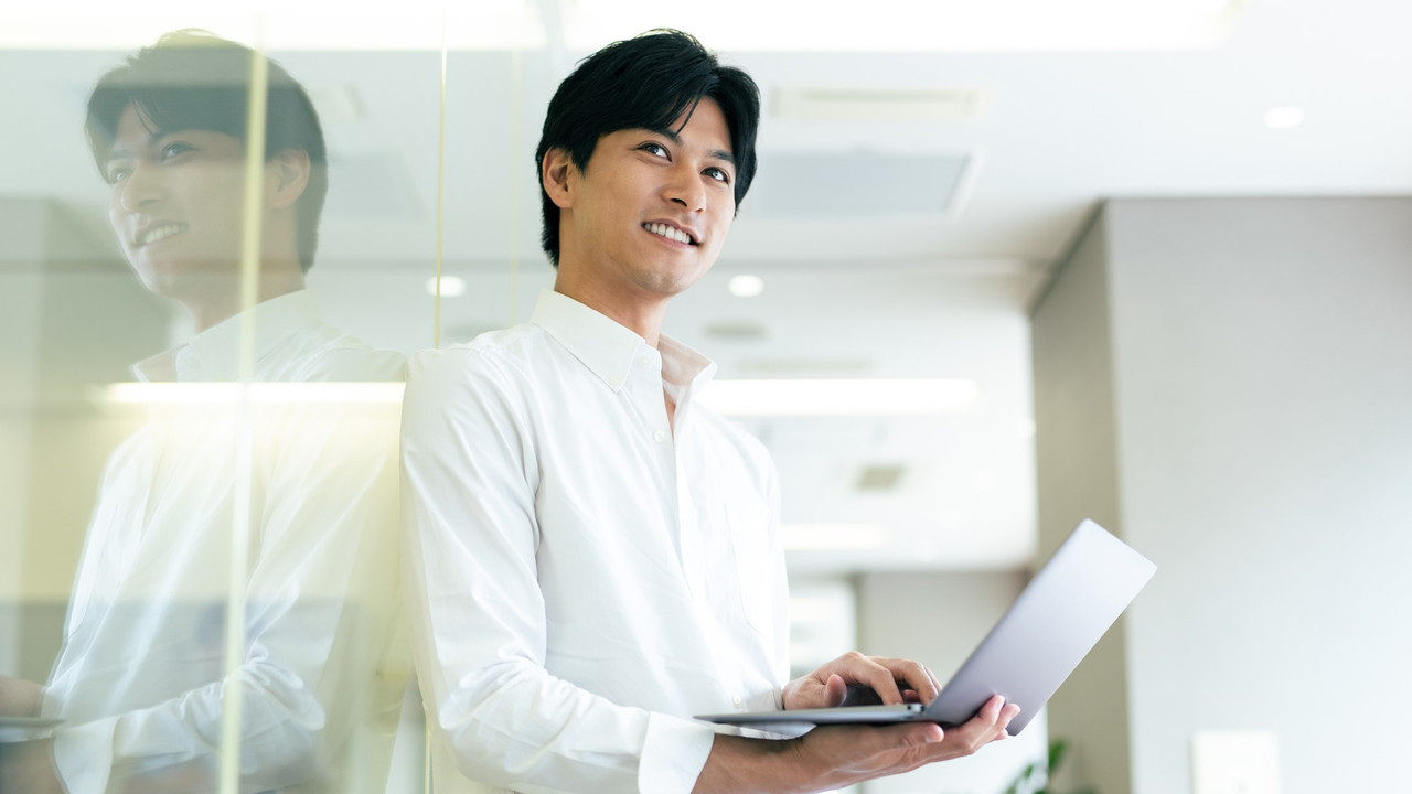 パソコンを持つ笑顔の男性